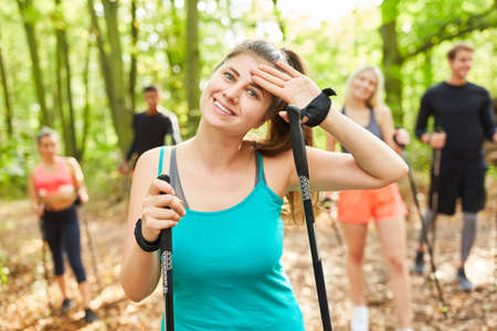 Sweating young woman after the strict Nordic walking course in nature