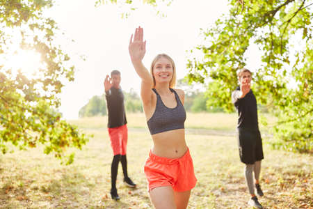 Group of young people has fun doing dance gymnastics in aerobics class in nature