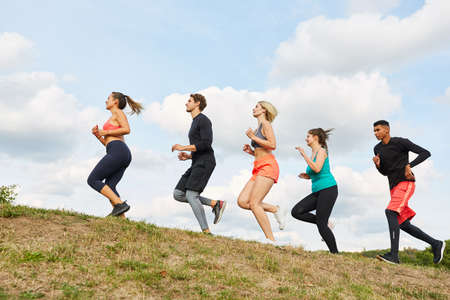 Group of young people trains endurance in cross-country or cross-country runs in nature