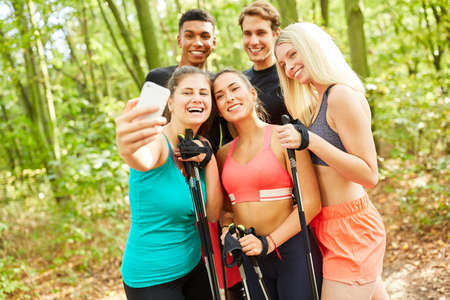 Group of friends takes a selfie photo during a Nordic walking excursion in summer