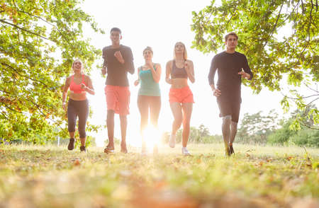 Group of friends jogging together outdoors in nature in summer Stock Photo
