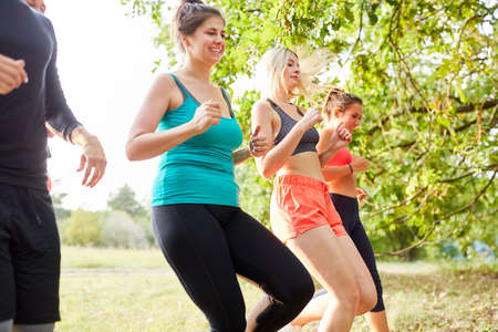 Group of young people jogging together in nature for endurance and health