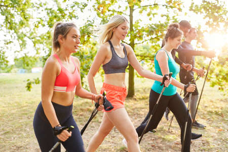Young people do Nordic Walking together as fitness and endurance training