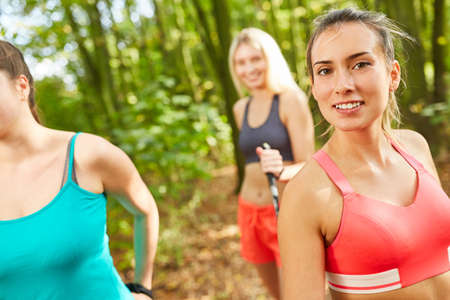Sporty young woman doing nordic walking with girlfriends for fitness and endurance