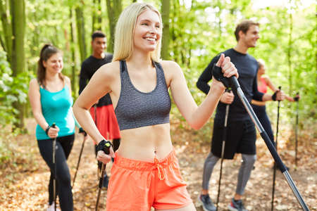Group of friends doing Nordic walking as endurance training in nature in summer
