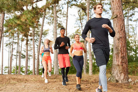 Young people in a running group doing endurance training in nature in the forest