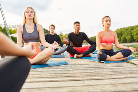 People do yoga together for relaxation in class outdoors in nature in summer 免版税图像