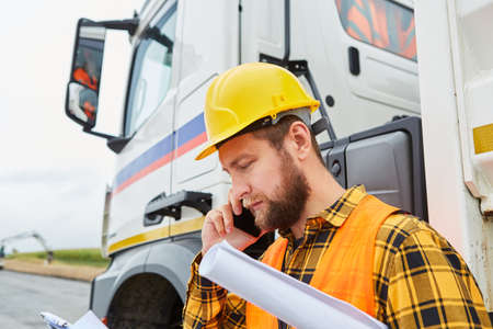 Construction worker calls in front of a truck with mobile phone on the construction site of the road construction