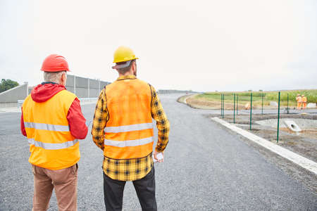 Two road construction workers inspecting a construction site for planning purposes