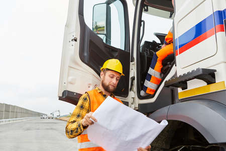 Road construction worker stands with a map at the truck with delivery of construction materials 免版税图像