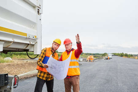 Architect and construction worker with site plan discuss development of new building area