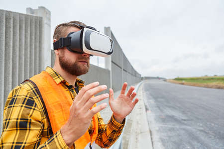 Worker with VR glasses during virtual construction planning on a construction site in the road construction of the future