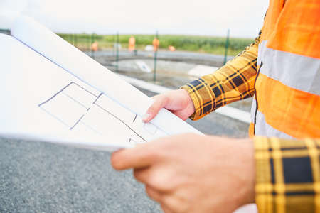 Construction worker with floor plan when planning the construction of a house in the new development area