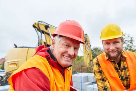 Smiling architect and construction worker on construction site of house building with excavator