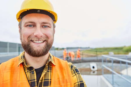 Smiling construction worker as a proud road builder on a construction site in the new development area
