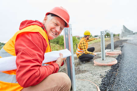 Smiling construction worker on construction site of road construction checks foundation for guardrails
