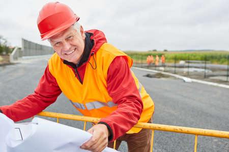 Construction manager or architect with floor plan or site plan on the road construction site
