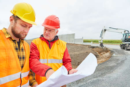 Architect and site manager with construction drawing on the construction site in road construction with excavator 免版税图像