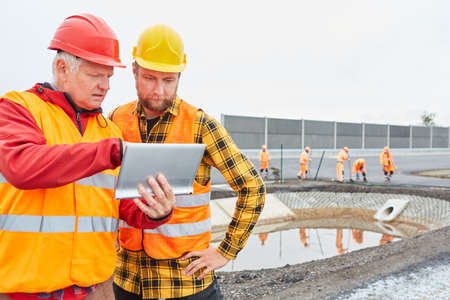 Architect and foreman with tablet PC during construction planning in front of an excavation