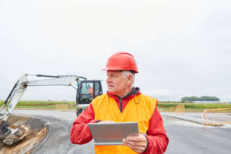 Construction worker with tablet computer on construction site in road construction in front of an excavator