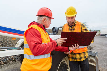 Architect and construction worker with documents on the construction site from road construction in front of a wheel loader