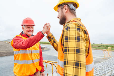 Two road construction workers celebrate success with handshake