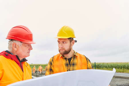 Construction workers and architects plan house or road construction with a blueprint in the new development area