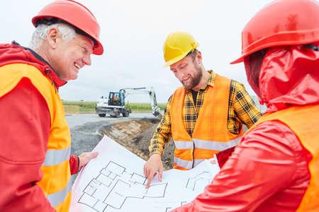 Construction workers team with floor plan during house construction planning on construction site with excavator 免版税图像