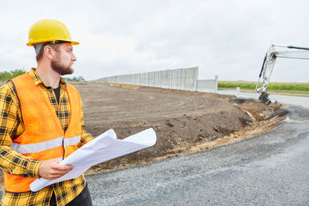 Construction workers in road construction with a site plan on the construction site for the new bypass road