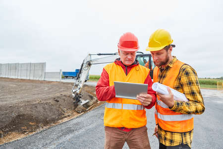 Construction worker and architect on construction site with planning on tablet PC in front of excavator 免版税图像