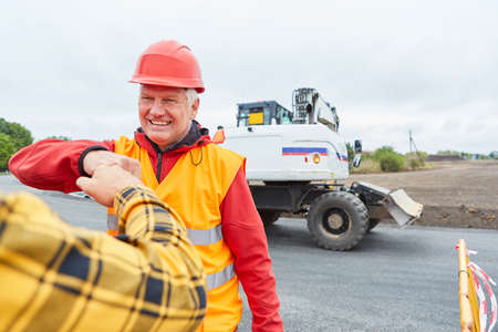 Construction worker greets colleagues with a fist bump on the construction site 免版税图像