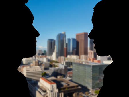 Two business people talking to each other in profile in front of the Los Angeles skyline