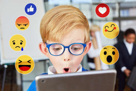 Child looks with surprise at computer monitor with social media reactions 免版税图像