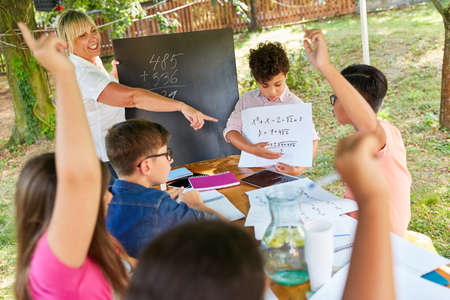 Teacher gives tutoring lessons in math for children in the summer school vacation course