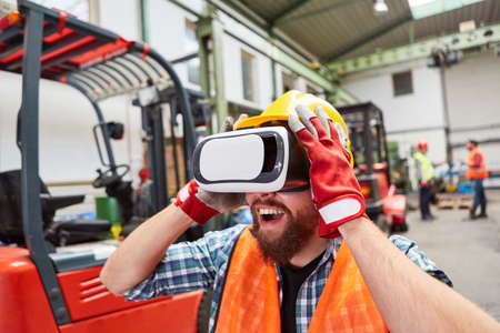 Amazed worker with VR glasses to visualize the factory of the future as virtual reality