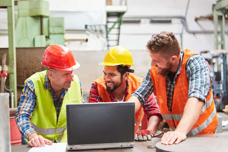 Three workers in factory together in front of laptop computer looking at email with order