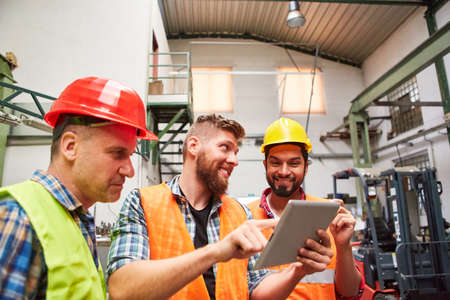 Group of workers in factory gets an order on the tablet computer