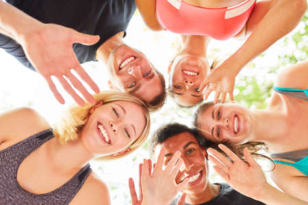 Group of young people happily waving at camera for friendship and team spirit