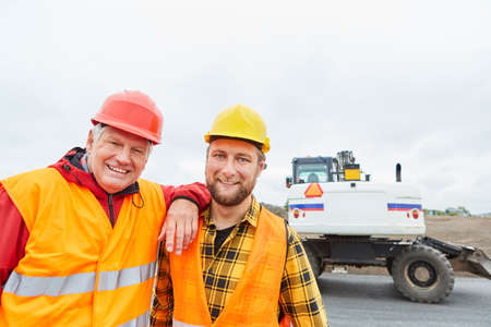 Construction workers as colleagues as a team on the construction site of road construction with excavators