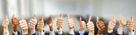 Business team with thumbs up in the office in a business meeting