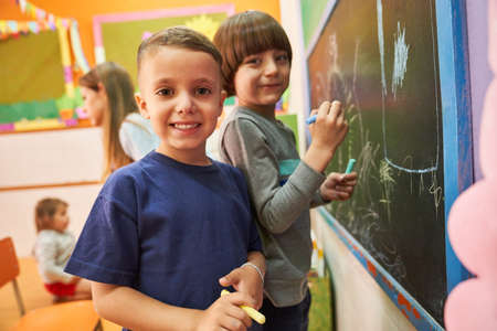 Children paint with chalk on the blackboard in preschool or elementary school in creative painting class Imagens