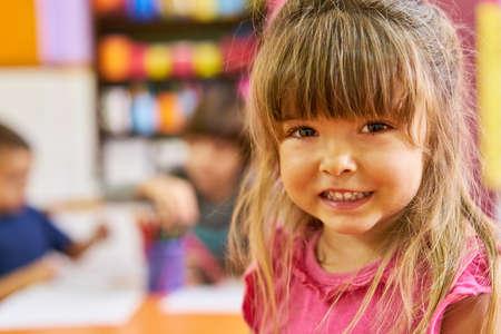 Cute girl in kindergarten or preschool is smiling at camera