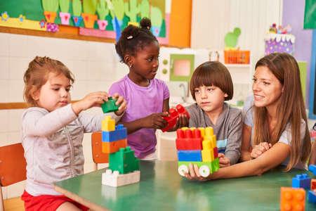 Childminder and children in international kindergarten play with building blocks