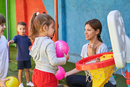 Sports teacher and children playing ball in sports class in daycare or preschool
