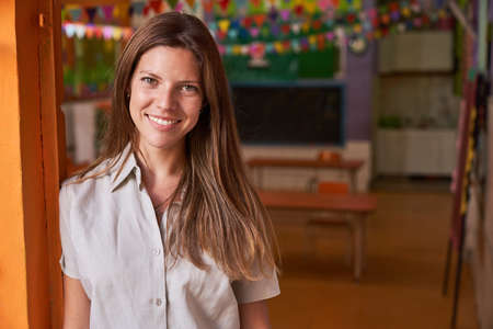 Young woman as a happy educator or kindergarten teacher in a day care center or after-school care center