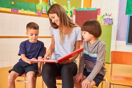 Kindergarten teacher and two children reading a book in daycare or preschool