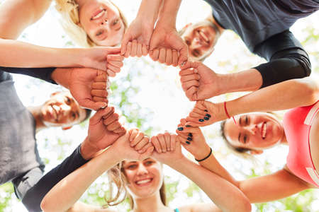 Group of friends with clenched fists in a circle for motivation and team building Imagens