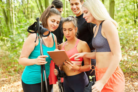 Group of young people looking at tablet computer while Nordic walking in nature