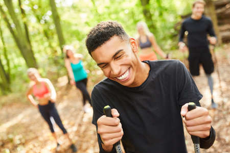 Young man as a Nordic walking trainer has fun doing sports with his group