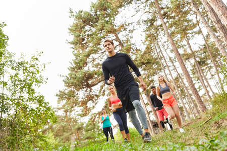 Group of friends at the endurance run in nature in the forest for stamina and fitness Imagens